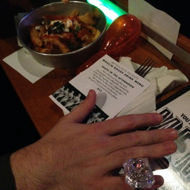 My hairy man-friend sporting our classy Moulin Rouge Sing-Along ring prop in exchange for me getting him some loaded fries, and the absinthe drink mix that is advertised in the picture, also.